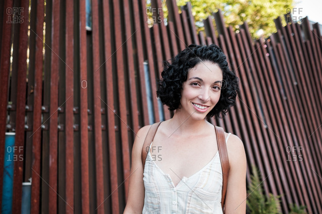 Portrait of a beautiful young woman with short curly hair standing by wooden fence