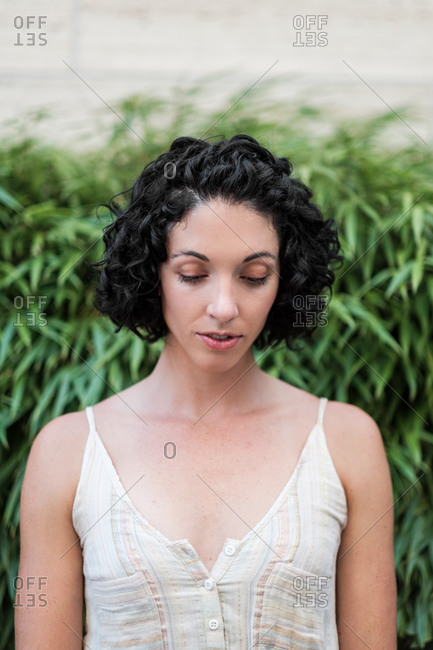 Portrait of a beautiful young woman with short curly hair looking down