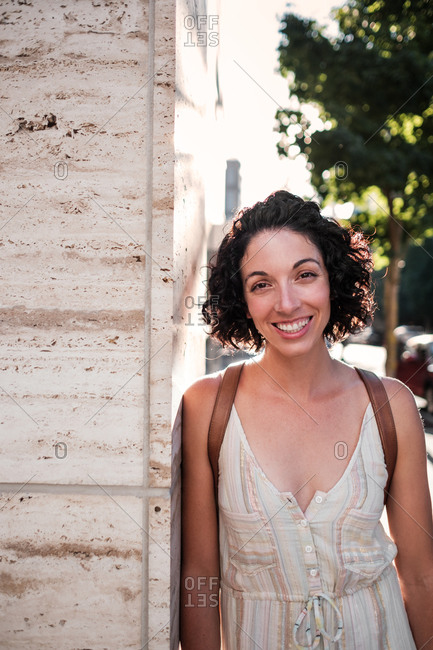 Portrait of a young woman with short curly hair walking around town on a sunny day