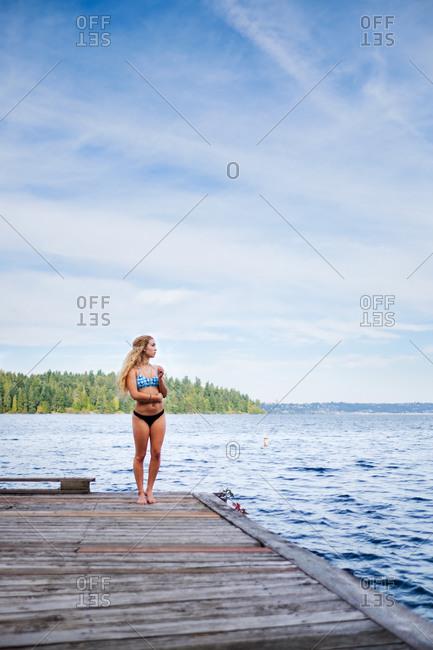 Blonde woman in a blue bikini standing on lake dock