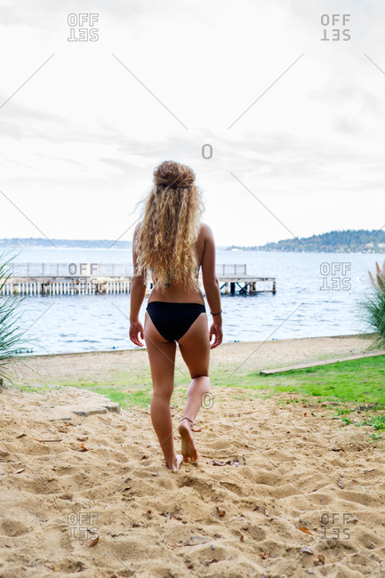 Rear view of a blonde woman in a bikini on lakeside beach