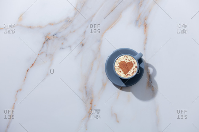 Cup of coffee with heart shape on a table