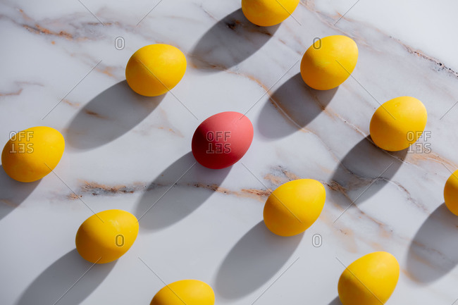 Yellow and one red easter eggs on marble background