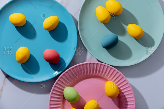 Multicolored easter eggs in a plates on a marble table