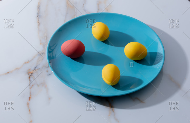 Easter red and yellow eggs in a blue plate on marble table