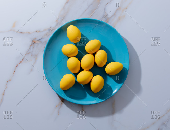 Yellow easter eggs in blue plate on marble table