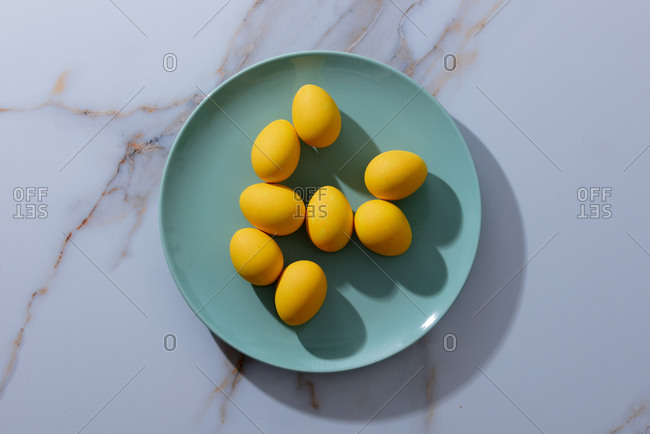 Yellow easter eggs in green plate on marble table