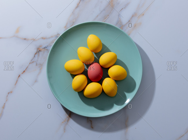Easter red and yellow eggs in a green plate on marble table
