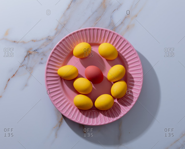 Yellow and red easter eggs in pink plate on marble table