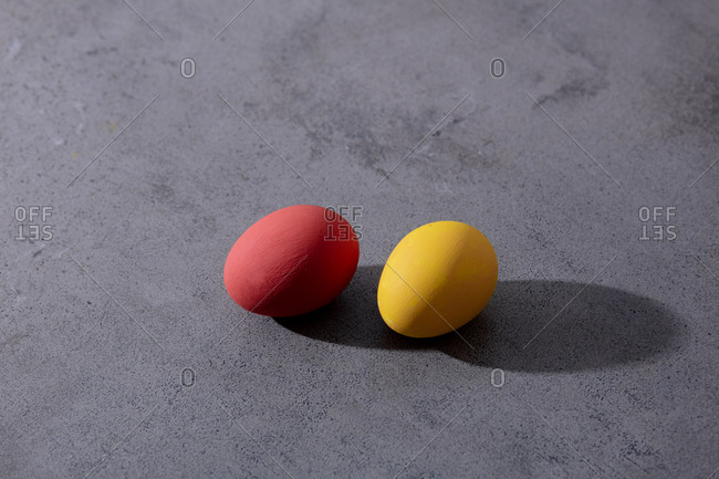 Red and yellow easter eggs on concrete surface