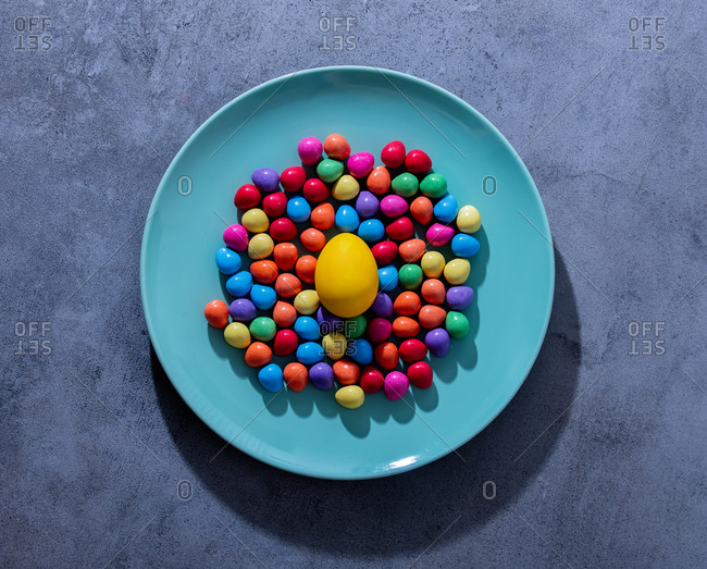 Easter egg and candies in a blue plate on gray background