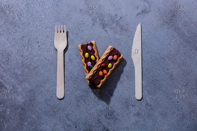 Cookies with dragee in chocolate and wooden knife with fork