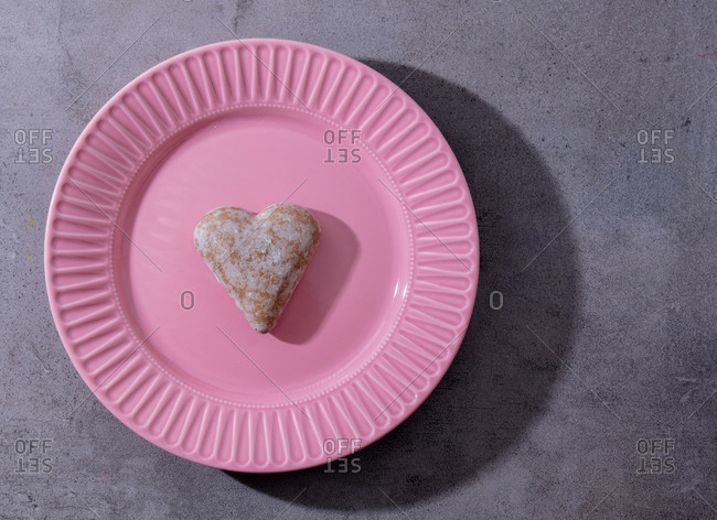 Heart shape gingerbread in pink plate on gray background