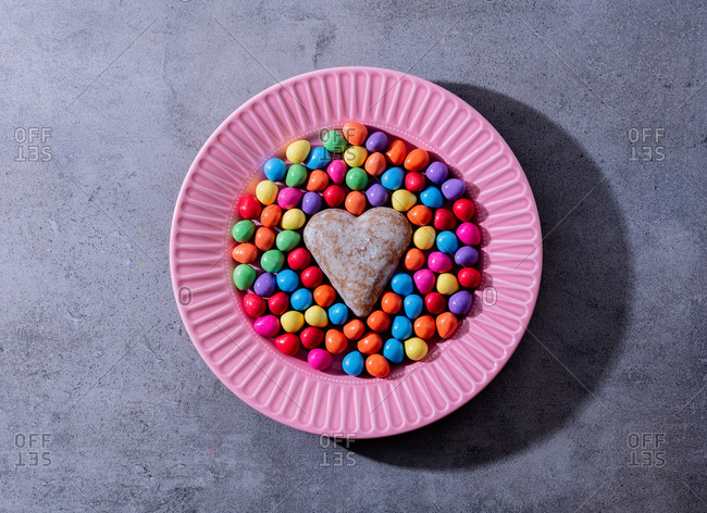 Heart shape gingerbread and easter eggs in pink plate on gray background