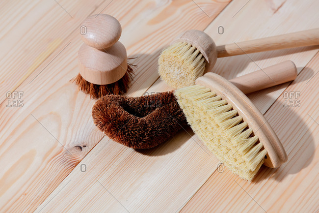 Eco-friendly wooden brushes for washing dishes on a wooden table