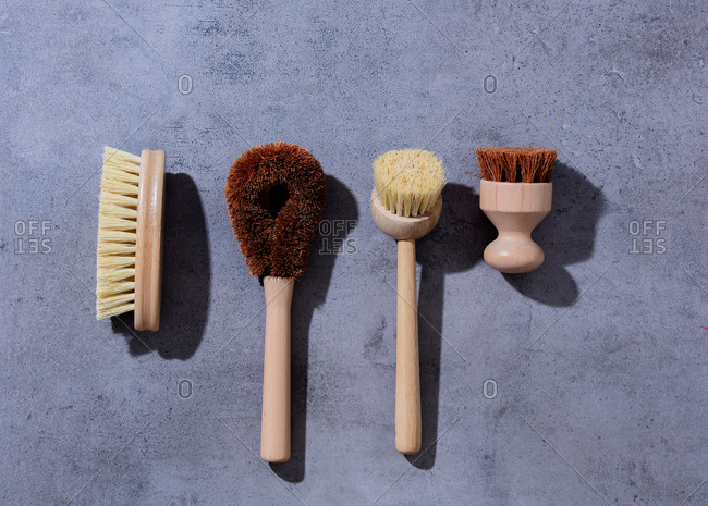 Eco-friendly wooden brushes for washing dishes on gray background