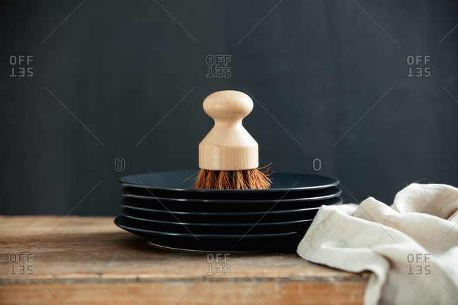 Eco-friendly wooden brush for washing dishes on a plates