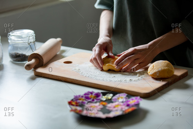 Woman making cookies with primula petals at kitchen table.