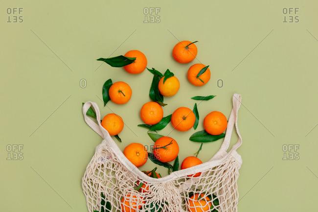 Fresh mandarins and string bag on green background