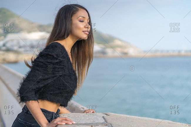 Mixed race woman looks at the sea from the promenade
