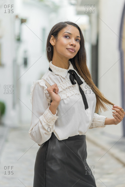 Elegant mixed-race woman looks look away in the street