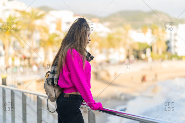 Pensive mixed-race woman in pink wool sweater facing the beach