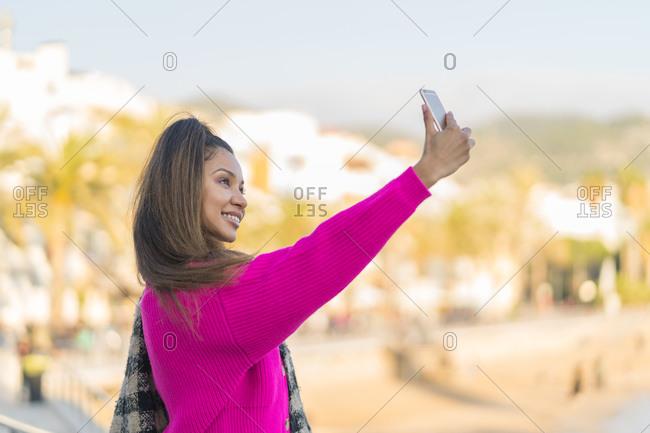 Happy mixed race woman dressed in pink wool sweater taking a selfie near seaside