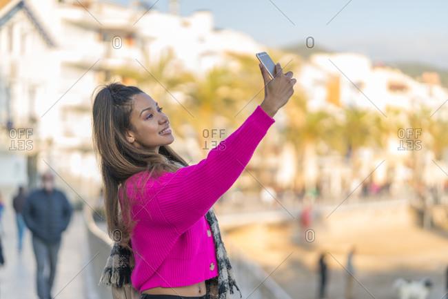 Happy mixed race woman taking selfie near seaside