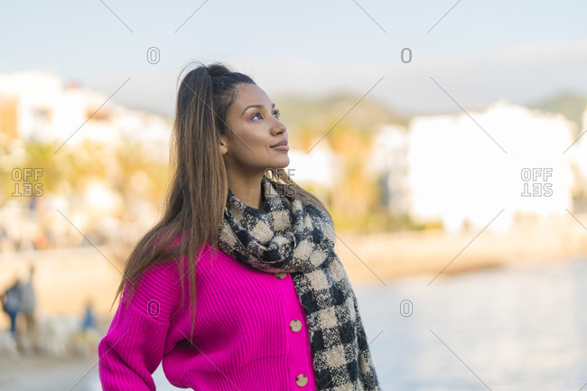 Mixed race woman dressed in a pink wool sweater looking at the sky