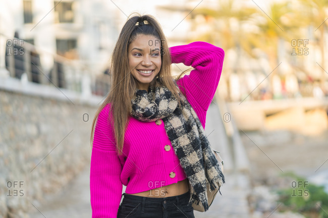 Very happy mixed race woman dressed in pink wool sweater near the beach