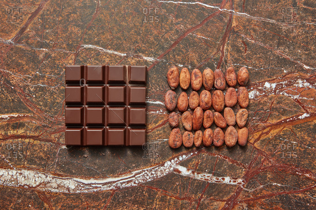 Two square pattern of cocoa beans and chocolate bar on a brown marble background