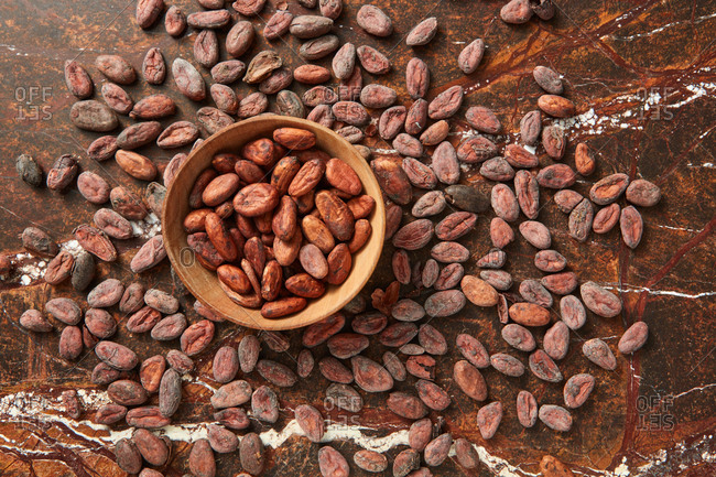 Freshly dried natural organic cocoa beans in a wooden bowl on a cacao peas background