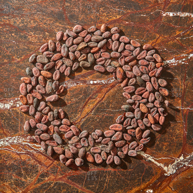 Freshly roasted natural organic cocoa beans in the shape of round frame on a brown marble background with copy space