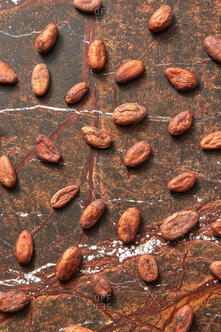 Freshly dried natural organic cocoa beans pattern on a brown marble background
