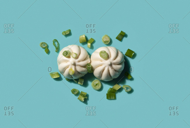 Steamed buns with chives on a teal blue background