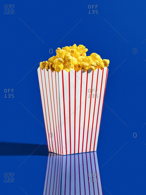 A box of yellow popcorn in a red and white striped box on a yellow background