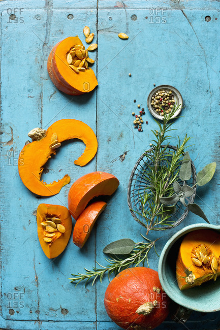 Slices of red kuri squash (Cucurbita maxima)- rosemary- sage and pepper lying on blue cutting board