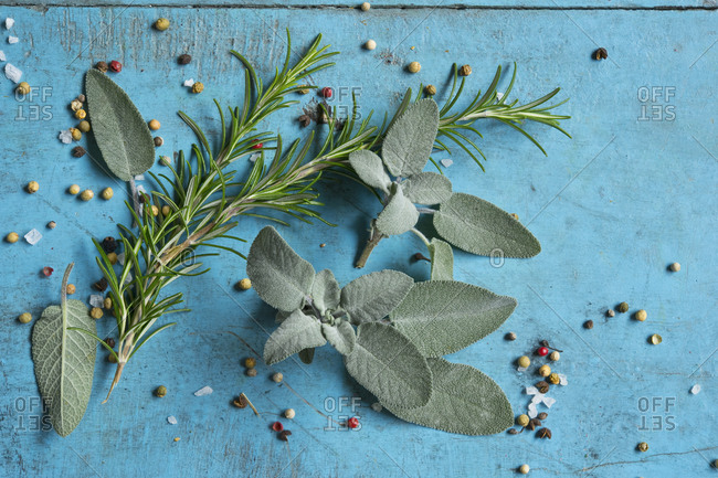 Rosemary- sage- salt and pepper lying on blue cutting board