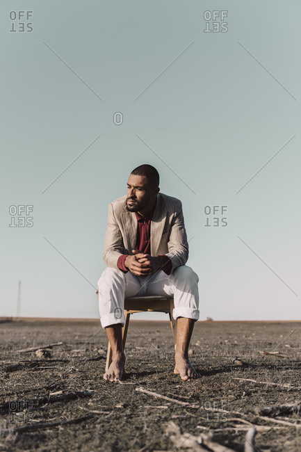 Young man sitting on chair in barren land
