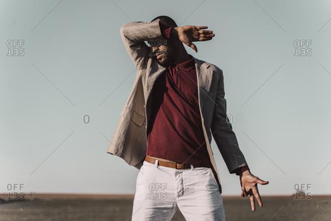 Young man standing in barren land shielding eyes