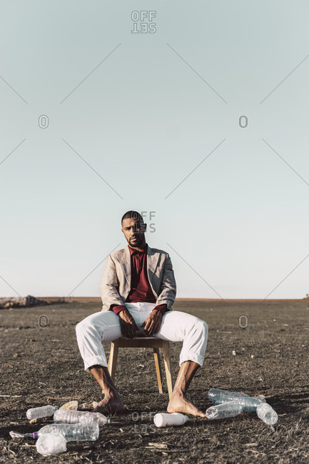 Young man sitting on chair surrounded by plastic bottles in barren land