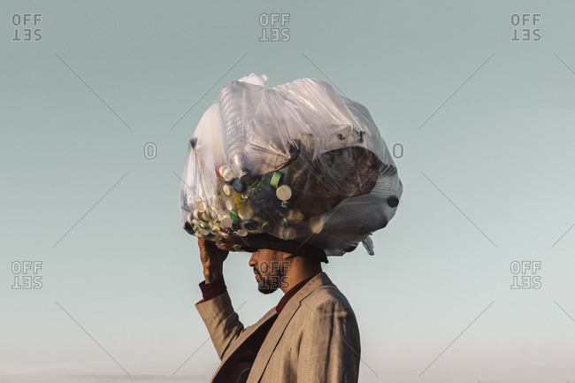 Young man carrying bag with plastic bottles under blue sky