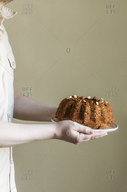 Mid section of man holding plate with zucchini cake