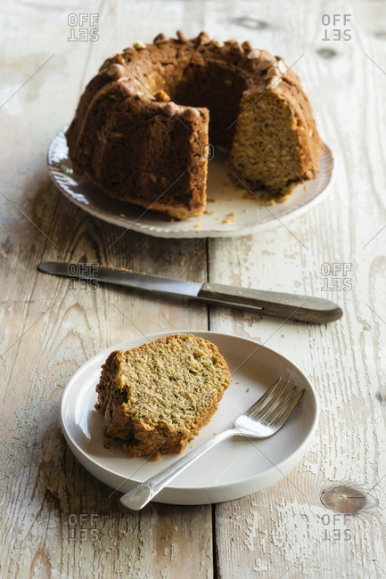 Slice of homemade zucchini cake with rest of cake in background