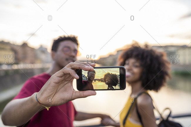 Young tourist couple taking a selfie on a bridge above river Arno at sunset- Florence- Italy