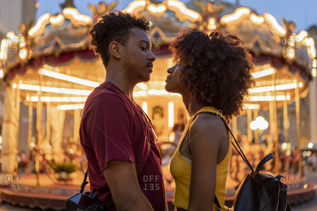 Affectionate young tourist couple at an illuminated carousel in the city at dusk- Florence- Italy