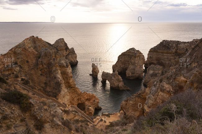 Portugal- Faro District- Lagos- Coastal cliffs and natural arch at sunrise