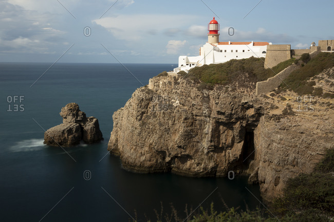 Portugal- Faro District- Lagos- Lighthouse standing at edge of coastal cliff