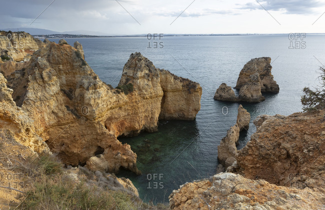 Portugal- Faro District- Lagos- Coastal cliffs at dawn with clear line of horizon over Atlantic Ocean in background