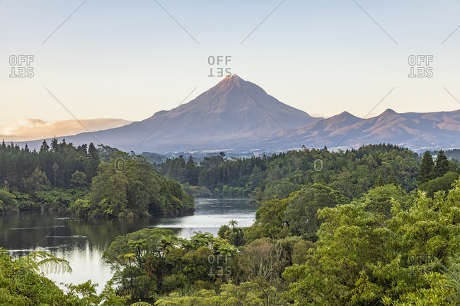 New Zealand- Scenic view of green forest surrounding Lake Mangamahoe with Mount Taranaki looming in background
